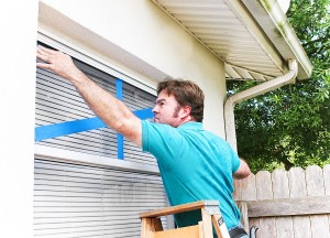 Man taping the windows on his home to protect from broken glass